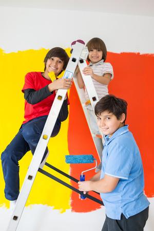 Niños ayudando: Niños que ayudan a la pared de la pintura en el hogar