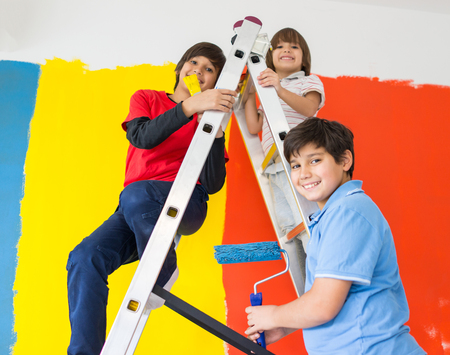 wall paint: Children helping painting wall at home Stock Photo