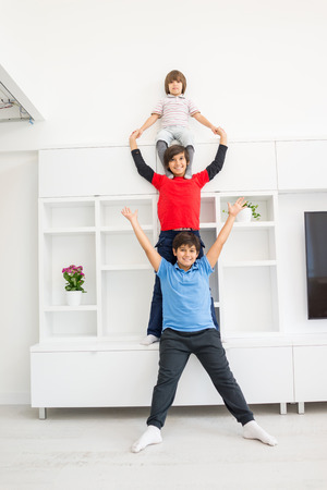 caras felices: Cheerful funny children having fun and posing line up piggyback in new modern home
