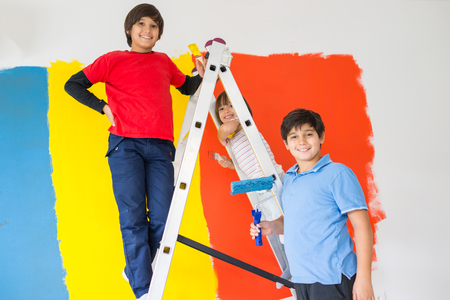 Children helping painting wall at home Stock Photo