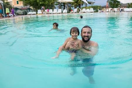 Young boy kid child splashing in swimming pool having fun leisure activity photo