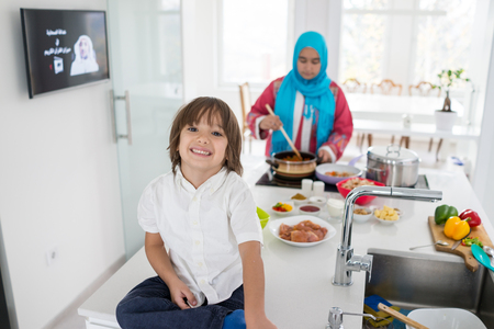 Muslim traditional woman with little son in modern white kitchen Stock Photo