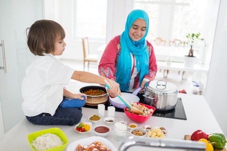 Muslim traditional woman with little son in modern white kitchen Imagens