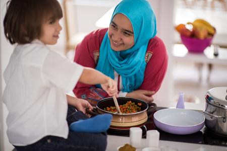イスラム教徒アラビア語、若い母親と幼いかわいい息子料理を作ると自宅の台所で楽しい