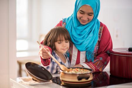 Arabische jonge vrouw met een klein kind in de keuken Stockfoto