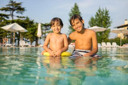 fun activity: Young boy kid child splashing in swimming pool having fun leisure activity