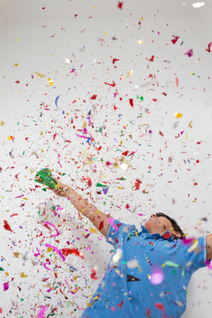 one year: Happy kid celebrating party with blowing confetti