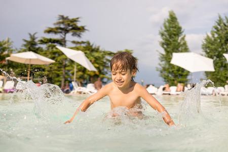 fun activity: Cute little boy kid child splashing in swimming pool having fun leisure activity