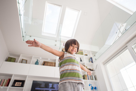 school boy: Happy kid at home with hands up