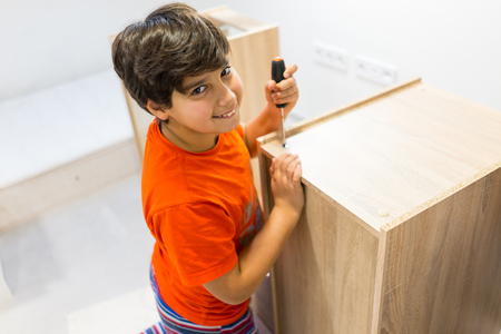 Happy kid at home constructing new furniture