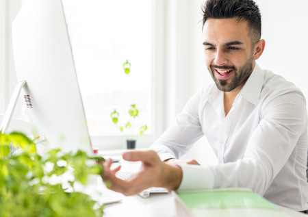 Young businessman working at office on computer desk