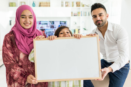 Happy Arabic Muslim family at modern home having fun and good time together holding white board for copy space message Stock Photo
