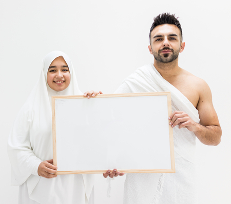 Muslim man posing as ready for Hajj visiting Kaaba in Mecca holding white board for copy space your text or image