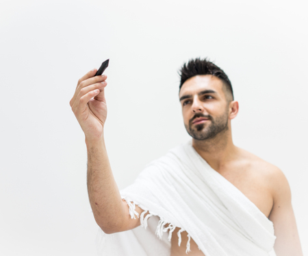 Muslim man posing as ready for Hajj visiting Kaaba in Mecca writing copy space for your text Stock Photo