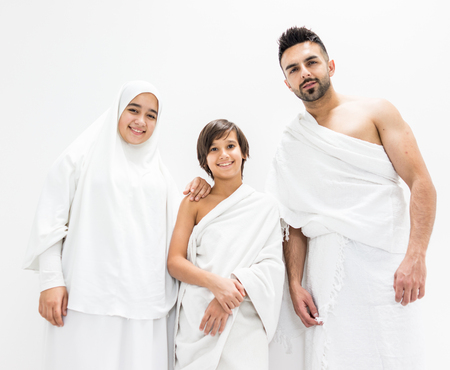 Muslim family posing as ready for Hajj visiting Kaaba in Mecca