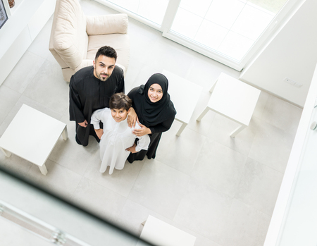 angle: High angle view portrait of happy Arabic Muslim family at new modern home Stock Photo