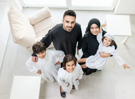 sitting on the ground: High angle view portrait of happy Arabic Muslim family at new modern home Stock Photo