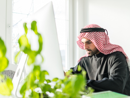 Arabian Gulf young businessman at office working on computer Stock Photo