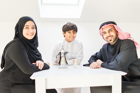 Happy Arabic family at dining room photo