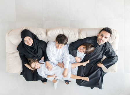 Happy Muslim family at modern home having fun and good time together photo