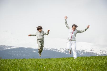 Jongen en meisje lopen op springveld in de Alpen