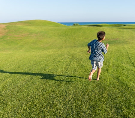 teen golf: Happy summer vacation for kids on green meadow near sea Foto de archivo