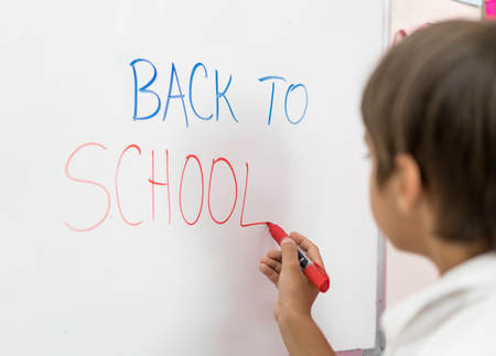 Boy writing on whiteboard Back to school