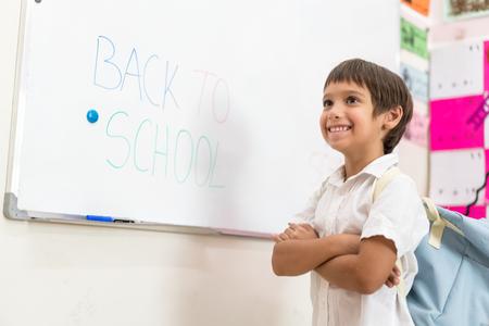 Boy writing on whiteboard Back to school