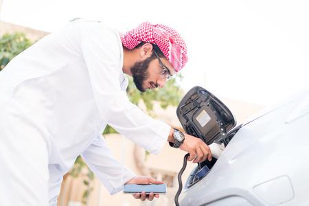 Young Arab man recharging electric car