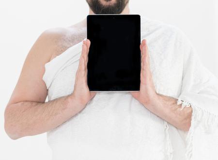Adult Hajj holding tablet Imagens