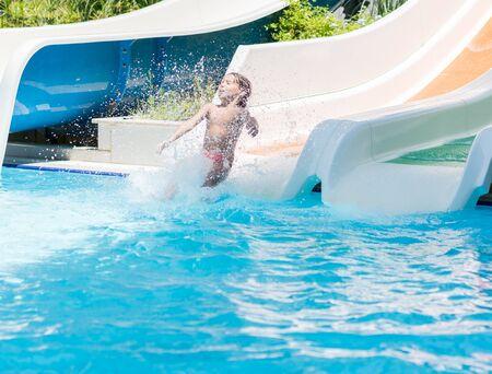 Children enjoying in pool water slide at pool
