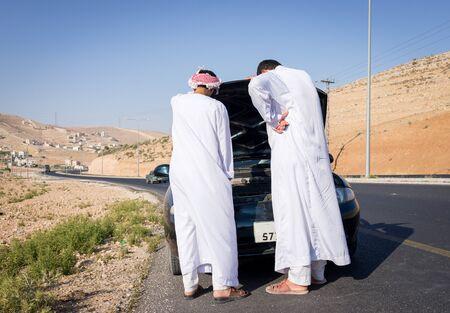 Deux jeunes hommes arabes ayant un problème de voiture sur la route Banque d'images