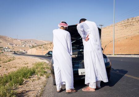 Two young Arab men having car issue on the road Stock Photo