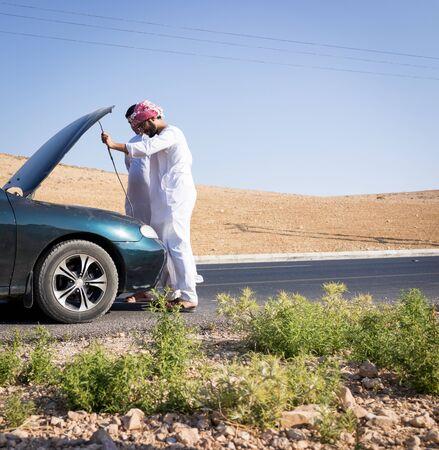 Deux jeunes hommes arabes ayant un problème de voiture sur la route