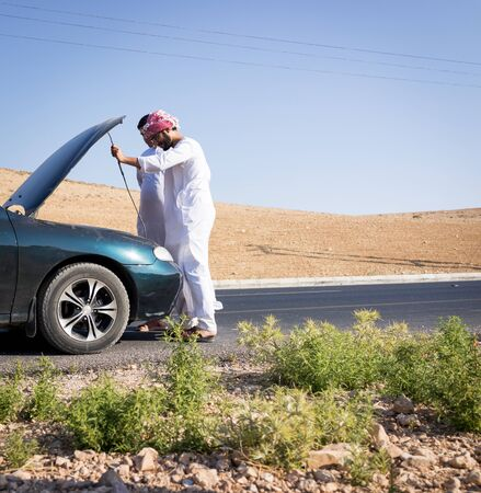 Two young Arab men having car issue on the road