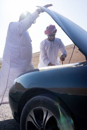 Two young Arab men having car issue on the road Standard-Bild