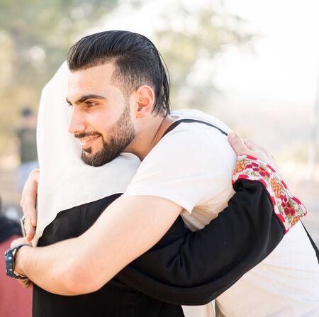 Muslimischer junger Mann umarmt seine Mutter
