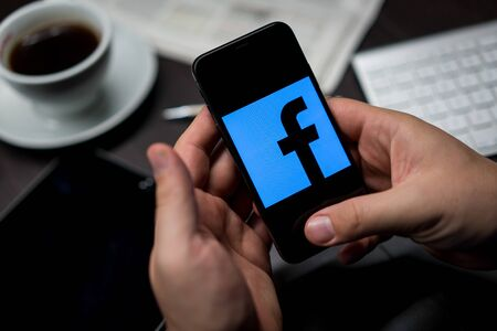 New York, New York / USA - 11 11 2019: Logo of Facebook on the iPhone X in hands in office