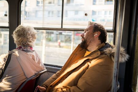 Man in public transport sitting with smartphone listening to music