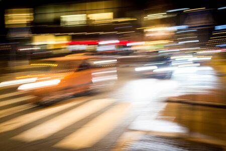 Mouvement de voitures sur la rue de nuit de pluie de ville