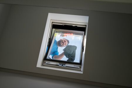 Man on loft window cleaning