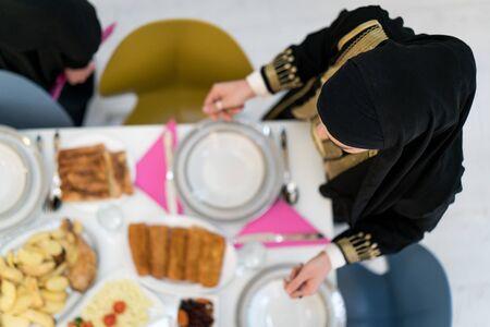 Muslim girls preparing table for family meal