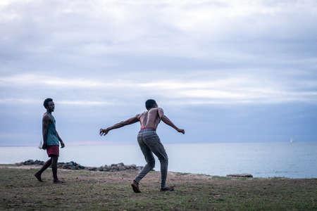 Young men exercising martial arts on the beach