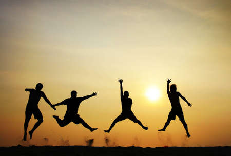 to have: 4 people jumping at the beach when sunset
