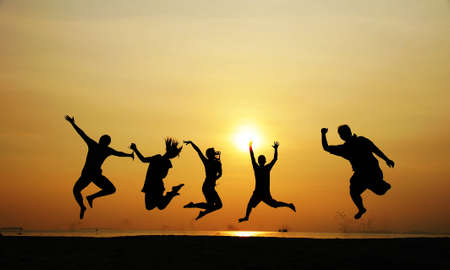 5 people jumping at the beach when sunset photo