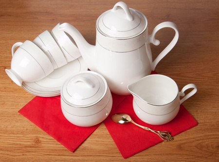 flatware: Bone china tea set on a wooden table