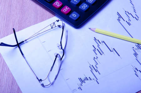 eyeglasses, calculator, pencil and diagram photo