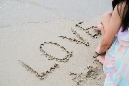big girl: Happy young woman on the beach writing love word Stock Photo