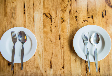 grunge flatware: white plat on wooden table Stock Photo