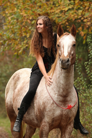 Amazing girl riding a horse without bridle in autumn Stockfoto